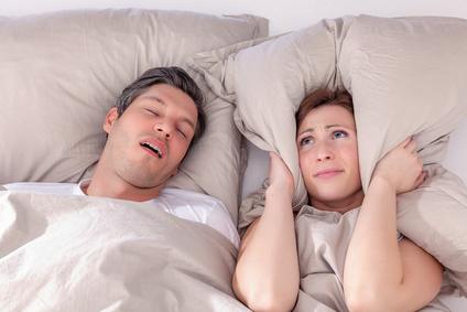 Eine Frau hält sich im Bett die Ohren zu, weil ihr Mann schnarcht